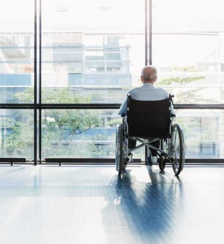 senior man in a wheelchair looking out of a window